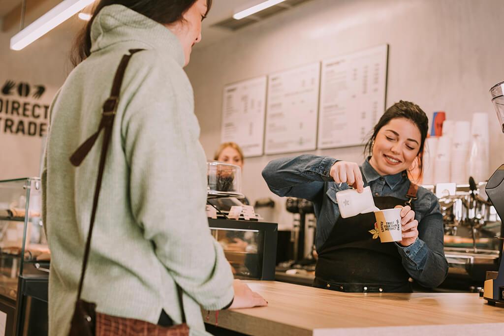 Coffee Island baristi pouring milk in the customer's coffee.