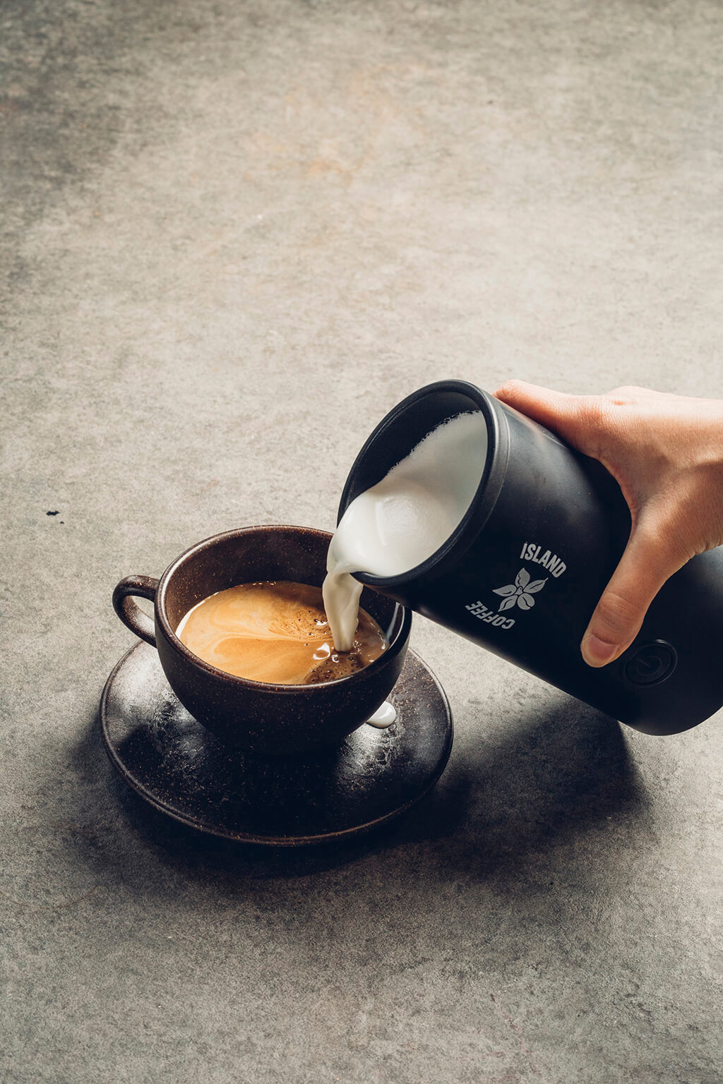 A woman pouring milk into a coffee island coffee.